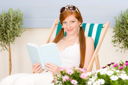 Summer terrace red hair woman relax in deckchair garden photo