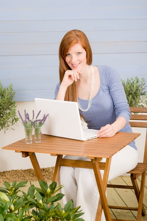 porches: Portrait redhead woman with laptop on terrace summer garden