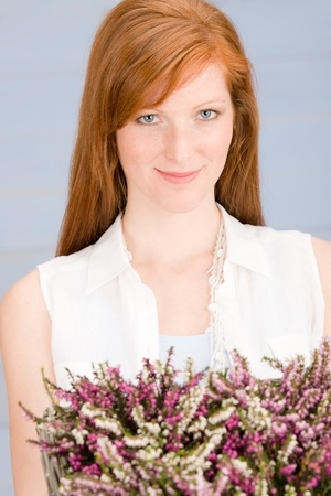 Summer close-up of redhead woman hold basket with flowers photo