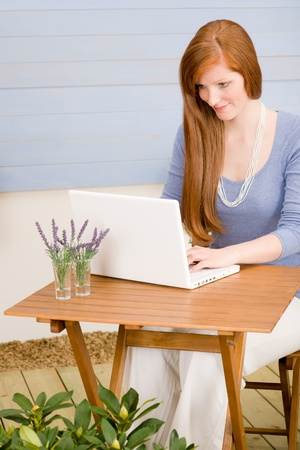 Summer terrace redhead woman with laptop in garden photo