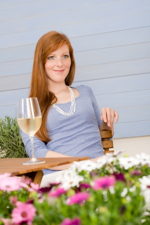Summer terrace redhead woman with glass of wine in garden photo