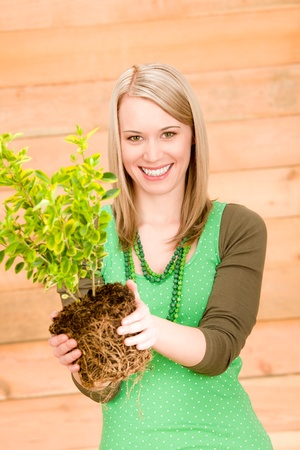 Portrait happy woman hold green plant spring gardening photo
