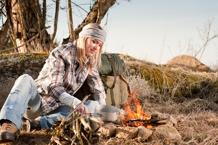 Campfire hiking woman with backpack cook in countryside photo