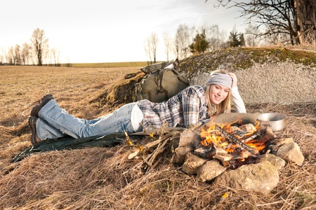 Campfire hiking woman with backpack sleep in countryside photo