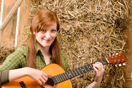 Young country red-hair woman playing guitar in barn photo