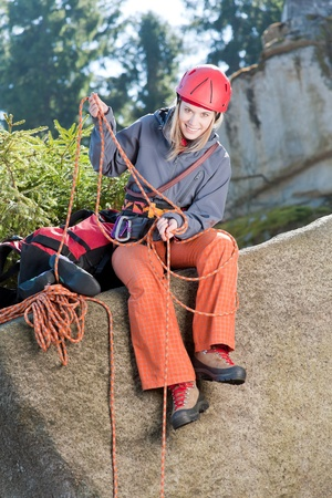 Active young woman prepare for rock climbing holding rope photo
