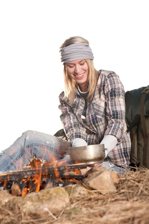 Young hiking woman with backpack cook on campfire in countryside photo