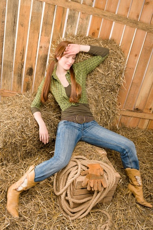 Provocative young cowgirl lying on hay in barn photo