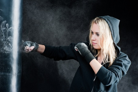 outfit: Blond boxing woman in black training with punching bag Stock Photo