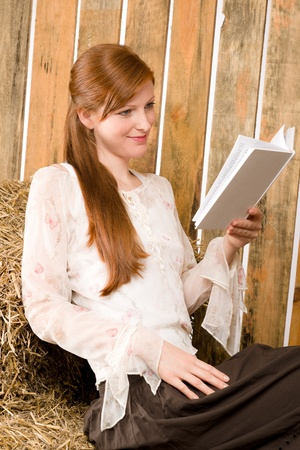 redhair: Young romantic red-hair woman reading book sitting in barn country