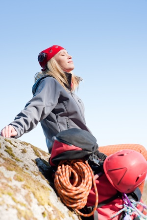 Active young woman rock climbing relax with backpack on mountain photo