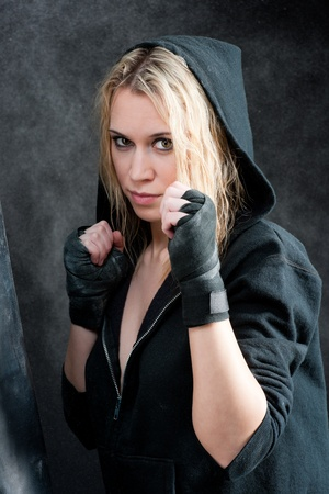 Tough boxing training woman in black grunge background photo
