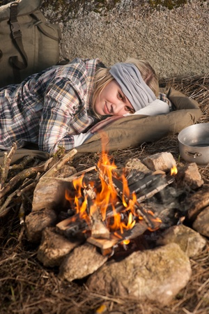 Young hiking woman with backpack sleep by campfire countryside Stock Photo - 9554029