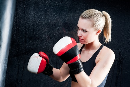 Boxing training woman with punching bag in gym wear gloves photo