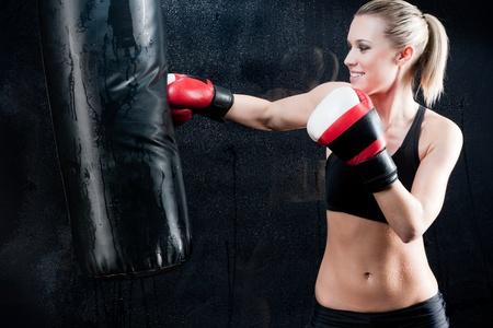 física: Mujer de entrenamiento de boxeo con saco de boxeo en guantes de desgaste de gimnasio