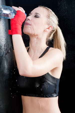 Boxing training woman pour water on face hold punching bag photo