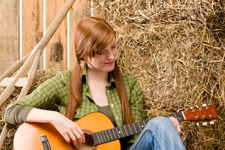 redhair: Young country red-hair woman playing guitar in barn Stock Photo