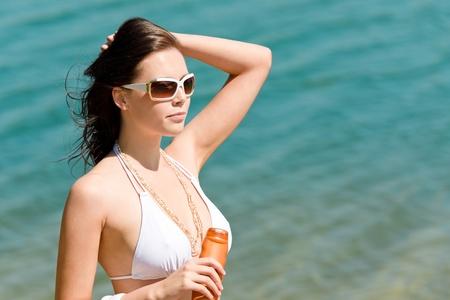 Summer sun young woman with suncream wear bikini enjoy photo