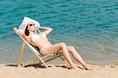 deckchair: Summer young woman sunbathing in bikini on beach