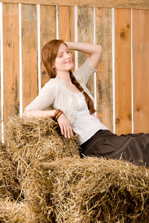 redhair: Portrait of romantic red-hair young woman sit on hay in barn Stock Photo