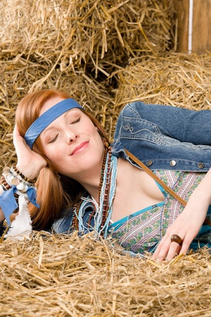 Young woman hippie style lying on hay in barn photo