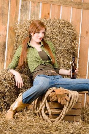 barn boots: Provocative young cowgirl drink beer in barn country style