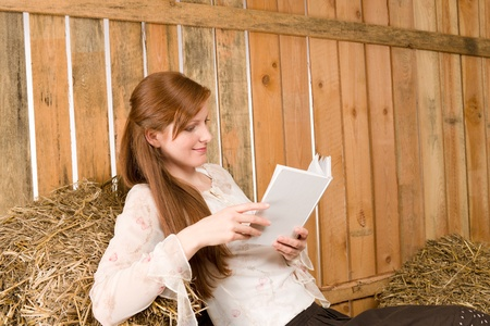 redhair: Young romantic red-hair woman hold book sitting in barn country Stock Photo