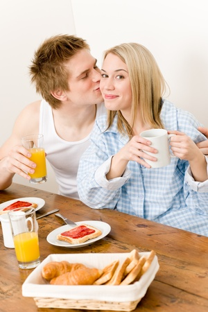 Breakfast happy couple enjoy romantic kiss in kitchen photo