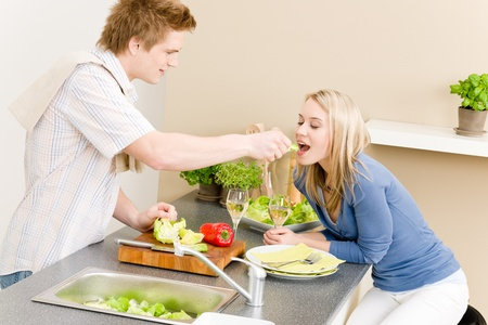 Lunch couple cook salad man feeding woman in kitchen photo
