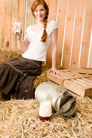 Young romantic woman with glass of natural milk in barn photo