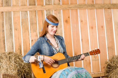 Young hippie woman play guitar sit on hay in barn photo