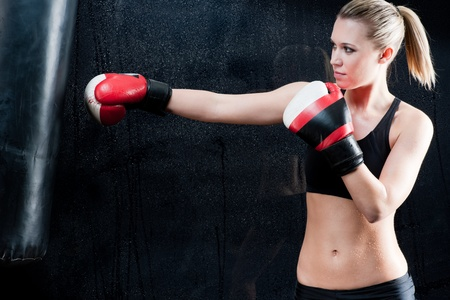 punching: Boxing training woman with punching bag in gym wear gloves