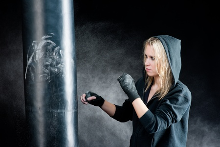 Blond boxing woman in black training with punching bag photo