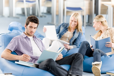Group of young high-school students relaxing with books and laptop Stock Photo - 9682663