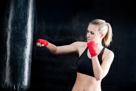 punching: Boxing training woman sparring punching bag in gym wear gloves Stock Photo