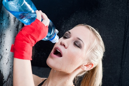 Boxing training woman pour water in her mouth photo
