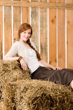 redhair: Portrait of romantic red-hair young woman sit on hay bales Stock Photo