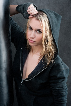 hoody: Blond boxing woman in black training with punching bag Stock Photo