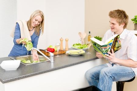 hombre cocinando: Pareja feliz almuerzo cocina a mujer ensalada de lechuga de lavado