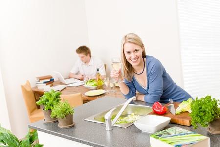 Happy woman cook enjoy white wine in kitchen, man in background photo