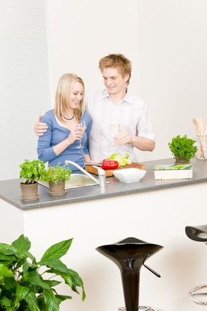 Lunch happy couple cook salad enjoy wine in kitchen photo