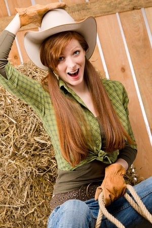 Crazy young cowgirl horse-riding country style in barn photo