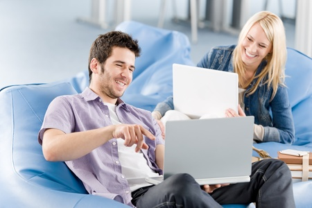 Young students at high-school relaxing pointing at laptop Stock Photo - 9682389