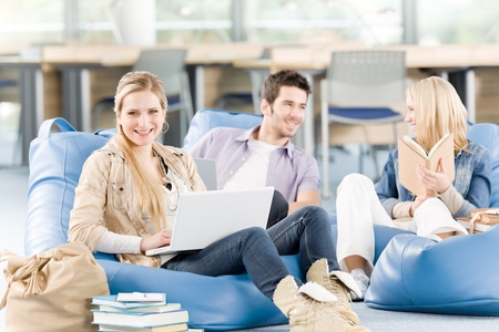 Group of young high-school students relaxing with books and laptop Stock Photo - 9682338