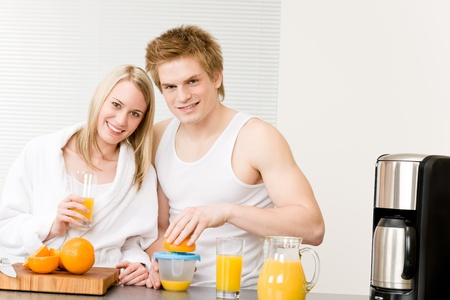Breakfast happy young couple make orange juice in morning kitchen photo
