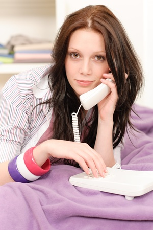 Portrait of young girl speaking on phone lying on bed photo