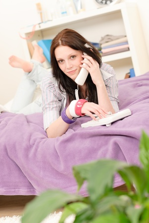 Student apartment - young girl speaking on phone lying on bed Stock Photo - 9682365