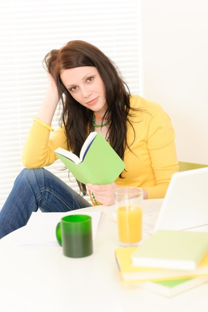 Young student girl reading book in student apartment photo