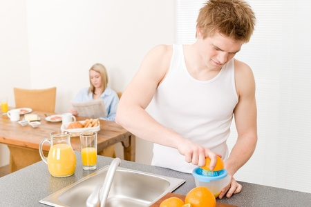 Breakfast happy couple make orange juice in morning kitchen photo