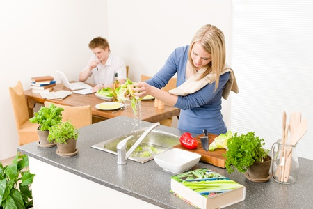 Lunch young woman cook salad wash lettuce, man in background photo